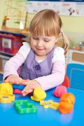 Female Pre School Pupil Playing With Modelling Clay - stock photo