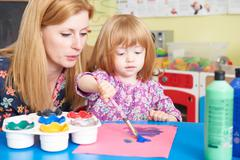 Teacher Helping Pre School Child In Art Class Stock Photos