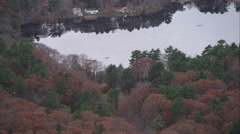 Over forested lakeshore and homes south of Norwood, Massachusetts. Shot in Stock Footage