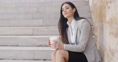 Grinning woman on stairs drinking coffee - stock footage