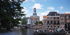 Floating restaurant in Leiden, The Netherlands; Hartebrug Church in background Stock Footage