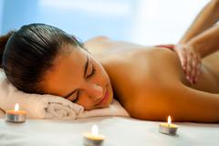 Attractive young woman having relaxing massage in spa. Stock Photos