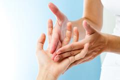 Detail of hands massaging hand. Stock Photos