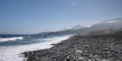 Waves rolling onto a rocky beach with hazy coastal hills in background Stock Footage