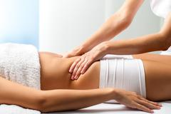 Therapist doing curative belly massage on female patient. Stock Photos