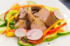 Delicious flank steak cuts cooked to perfection, mixed with reddish, zucchini - stock photo