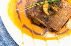 Delicious sirloin steak placed upon a bed of curry sauce on white dinner plate - stock photo