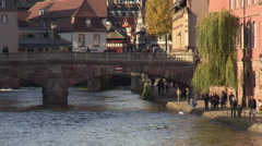Bridge in center of Strasbourg with people strolling on channel embankment - stock footage