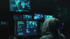 Male hacker in a hood works on a computer with maps and data on display screens Stock Footage