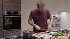 The man in the kitchen cut off the fins of a fish Stock Footage