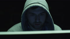 Portrait footage of concentrated male employee wearing a hood and working on pc - stock footage