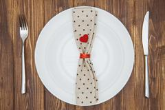 Valentine's day dinner setting, Knife, fork, napkin and plate - stock photo