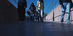 Several young adults walking toward camera on an outdoor walkway - stock footage