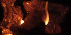 Close-up flames over a chunk of glowing wood on a fire Stock Footage