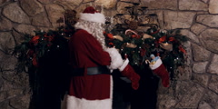 Santa Claus filling stockings hung above a decorated fireplace Stock Footage