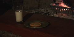 Milk and a cookie left on a hearth near a glowing fire; gloved hand taking Stock Footage