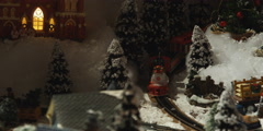 A tabletop Christmas village; Santa's hand setting toy train in motion Stock Footage