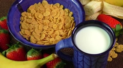 Healthy breakfast. Cornflakes, fresh strawberries, banana and milk - stock footage