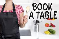 book a table cook holding wooden spoon concept - stock photo