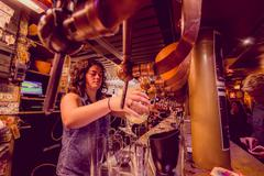 BRUSSELS, BELGIUM - 11 AUGUST, 2015: Bartender at Delirium Bar tapping beer into Stock Photos