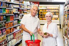 Senior couple holding oil bottle - stock photo