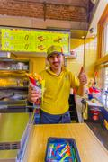 BRUSSELS, BELGIUM - 11 AUGUST, 2015: Fastfood worker showing traditional Belgian Stock Photos