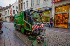 BRUSSELS, BELGIUM - 11 AUGUST, 2015: Green sweep truck passing through city Stock Photos