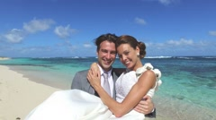 Groom holding bride in arms at the beach, turning around Stock Footage