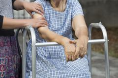 Elderly physical therapy by caregiver in backyard at home Stock Photos