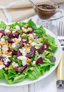 Salad with beets, feta cheese and walnuts, dressed with balsamic sauce - stock photo