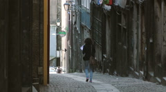 Single woman walking in the narrow street new city Stock Footage
