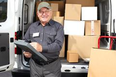 Senior delivery man with parcel near truck. Stock Photos