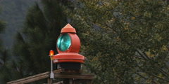 Close-up of a turning signal light at the top of a high platform near trees Stock Footage