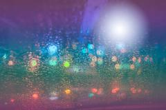 Raindrops on car glass at night Stock Photos