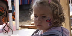 Little girl having her face painted at a carnival Stock Footage