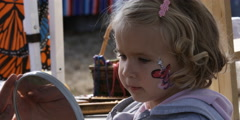 Little girl looking into a mirror at the design painted on her cheek - stock footage