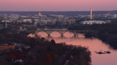 Flying past the Key Bridge over the Potomac River at dusk in Washington DC; left Stock Footage