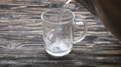 Glass of tea with teabag and pouring water Stock Footage