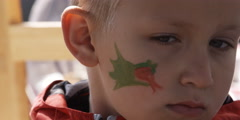 Close-up of a little boy getting his face painted Stock Footage