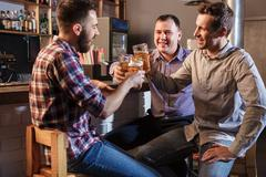 Stock Photo of Happy friends drinking beer at counter in pub