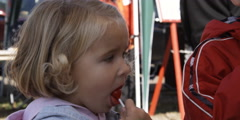 Close-up of a little girl licking a lollipop - stock footage