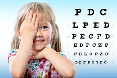 Cute little girl reviewing eyesight on chart. Stock Photos