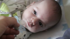 Teaching baby to take pacifier - stock footage