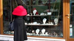 A woman with a red scarf standing near shop window of a jewelry store Stock Footage