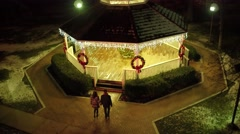 Aerial shot of young couple walking into gazebo during the Christmas holiday Stock Footage