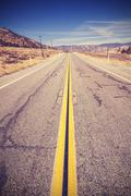 Vintage toned lanes on endless country highway, USA. - stock photo