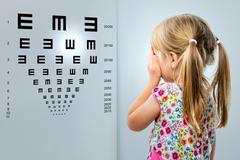 Little girl looking at vision test chart. Stock Photos