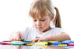 Little girl playing with puzzle pieces. - stock photo
