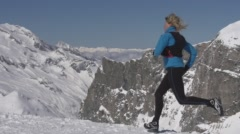 Woman Jogging across Mountain Peaks and Summits. Stock Footage