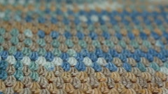 Close up of knitted wrap. Blue, gray, brown and white fabric texture background Stock Footage